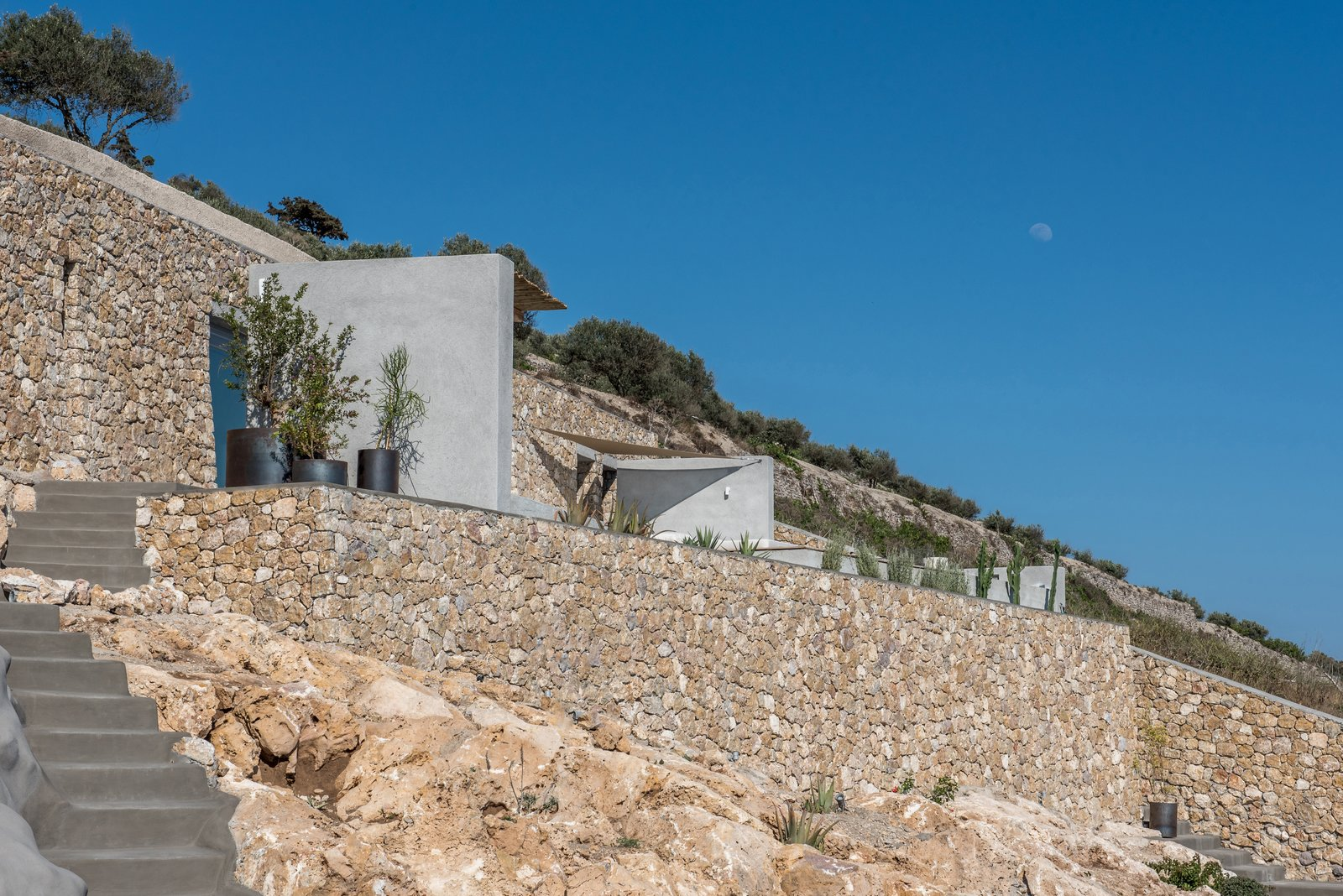Exterior, Concrete Siding Material, Stone Siding Material, House Building Type, and Flat RoofLine Free-standing concrete walls along the terrace delineates the two lateral staircases, directing the eye toward the captivating sea beyond.    Photo 4 of 18 in A Modern Home Is Gently Slotted Into a Steep Slope in Santorini