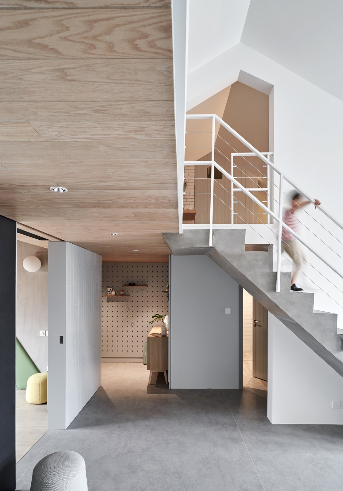 Hallway and Concrete Floor The open sliding doors of the kitchen and children's room can flexibly stretch the space, and when fully opened, improve circulation.    Photos from A Loft Mezzanine Cleverly Enlarges This Small Beijing Flat
