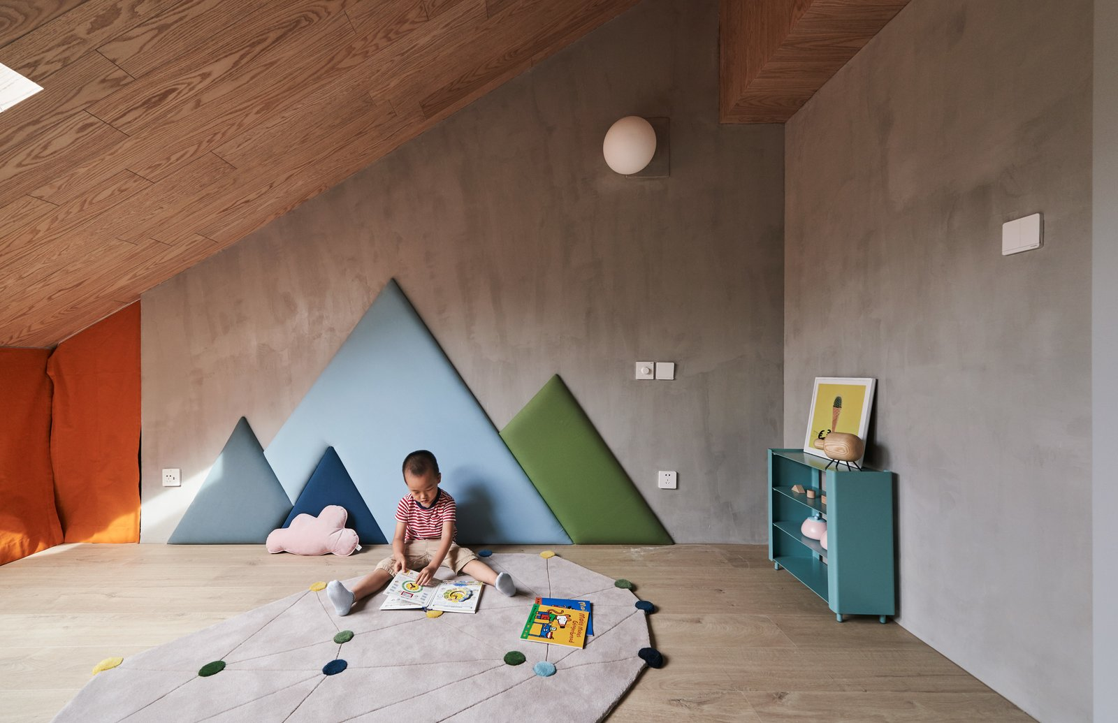 Kids Room, Rug Floor, and Light Hardwood Floor Mountain-shaped wall cushions line the wall of this cloistered playroom, echoing the peaked ceiling of the apartment.    Best Photos from A Loft Mezzanine Cleverly Enlarges This Small Beijing Flat