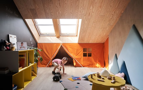 Awkward sloping ceilings are put to good use in this family apartment known as the Starburst House in Beijing, China. Across from the living lounge, tucked under the mezzanine study, is a child's playroom. Mountain-shaped wall cushions line the wall, echoing the peaked ceiling.