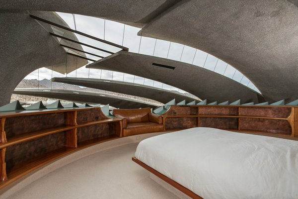 The circular master bedroom is supported by an illuminated, mushroom-shaped structure.