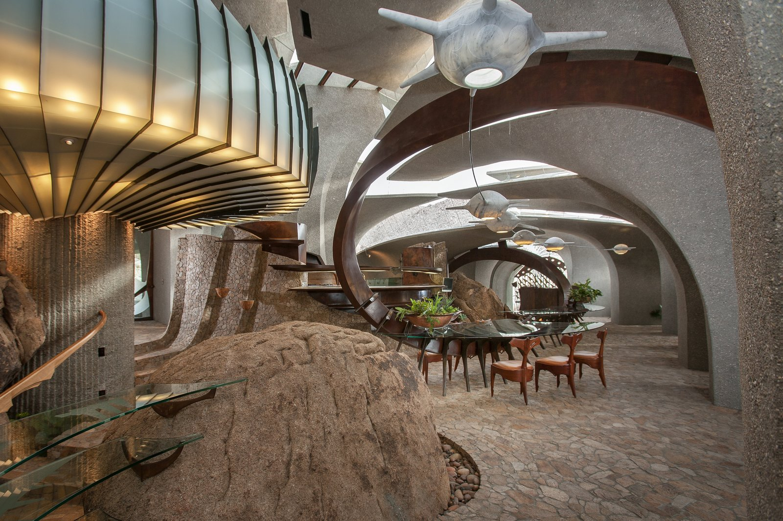High Desert House interior dining area with cement and stone curved walls and floors.