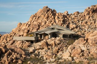 """Upon purchasing a 10-acre plot surrounded by a cluster of boulders, a couple wrote a handwritten letter to architect Kendrick Bangs Kellogg, which resulted in the 5,000-square-foot High Desert House on the edge of Joshua Tree National Park. Kellog spent five years designing a home that would settle into the landscape, """"crouching on the rocks, maybe like an animal asleep."""" The house features 26 freestanding concrete columns reminiscent of rib bones, and a glass ceiling that fills the home with daylight and views of the stars at night."""