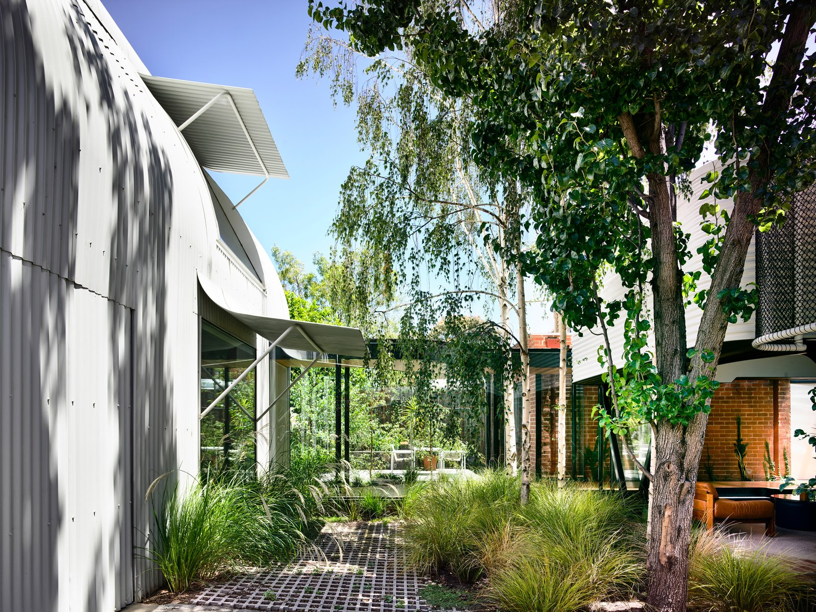 Outdoor, Shrubs, Grass, Trees, and Small Patio, Porch, Deck They unified the main house, rear stable and a new pavilion in the garden with corrugated colorbond steel metal cladding.  Photo 4 of 19 in An Inventive Melbourne Remodel Greets the Street With a New Garden