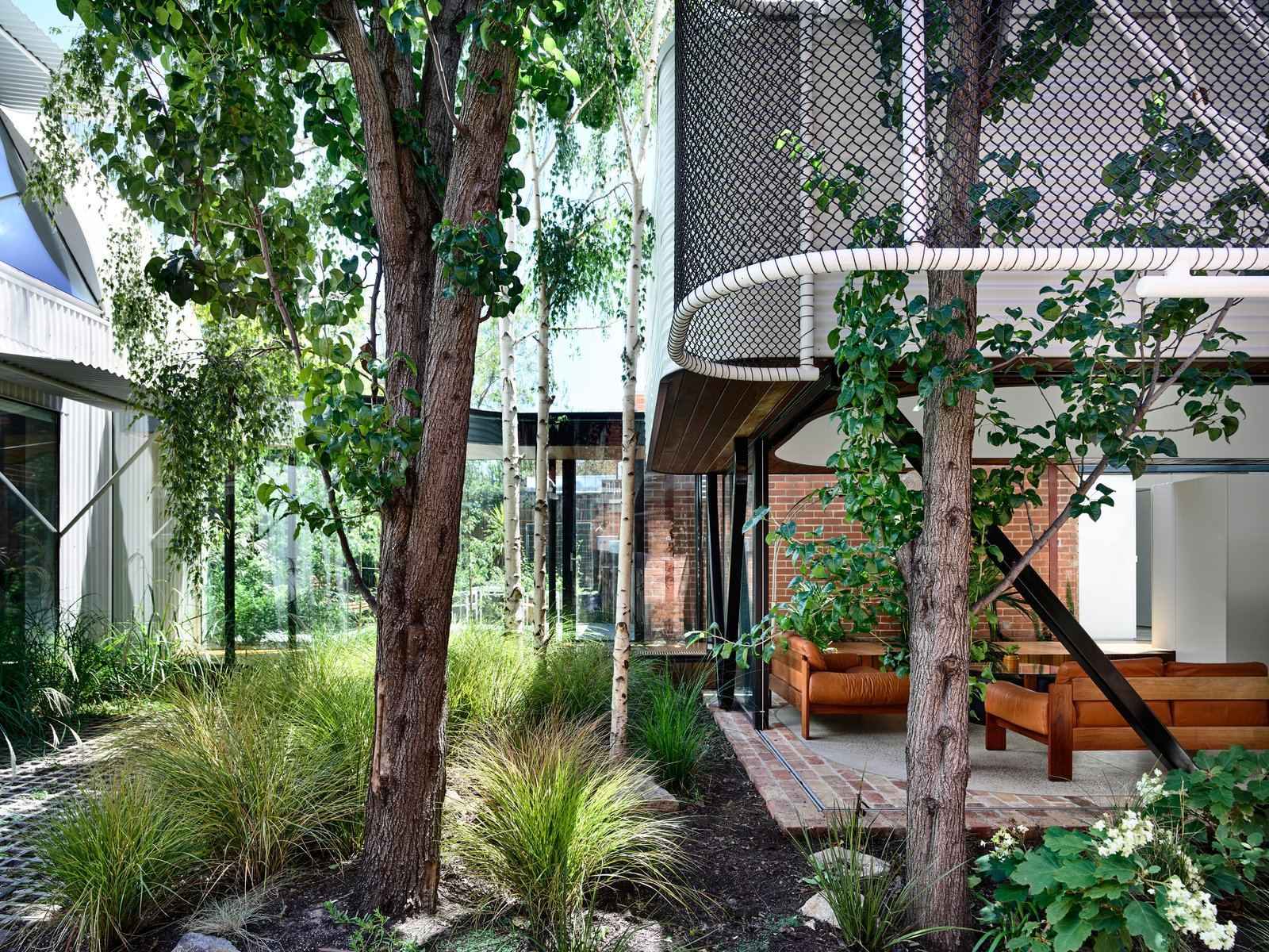 Outdoor, Small Patio, Porch, Deck, Grass, Trees, Shrubs, and Flowers Perforations were added to the boundary wall on the east, and entrance was moved to the side to become a bright corridor that connects the old house with the stable and pavilions.  Photo 3 of 19 in An Inventive Melbourne Remodel Greets the Street With a New Garden