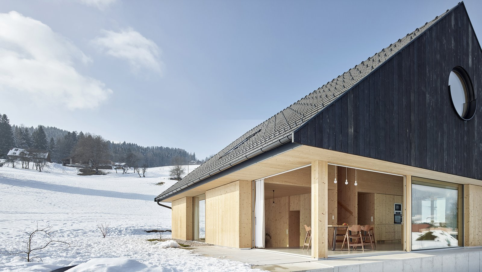 Exterior, House Building Type, Gable RoofLine, Wood Siding Material, Shingles Roof Material, Metal Roof Material, and Cabin Building Type The home has warm interiors throughout and boasts a minimalist, cabin-like aesthetic.    Best Photos from This Sleek Austrian Home Turns Into a Cozy Light Box at Night
