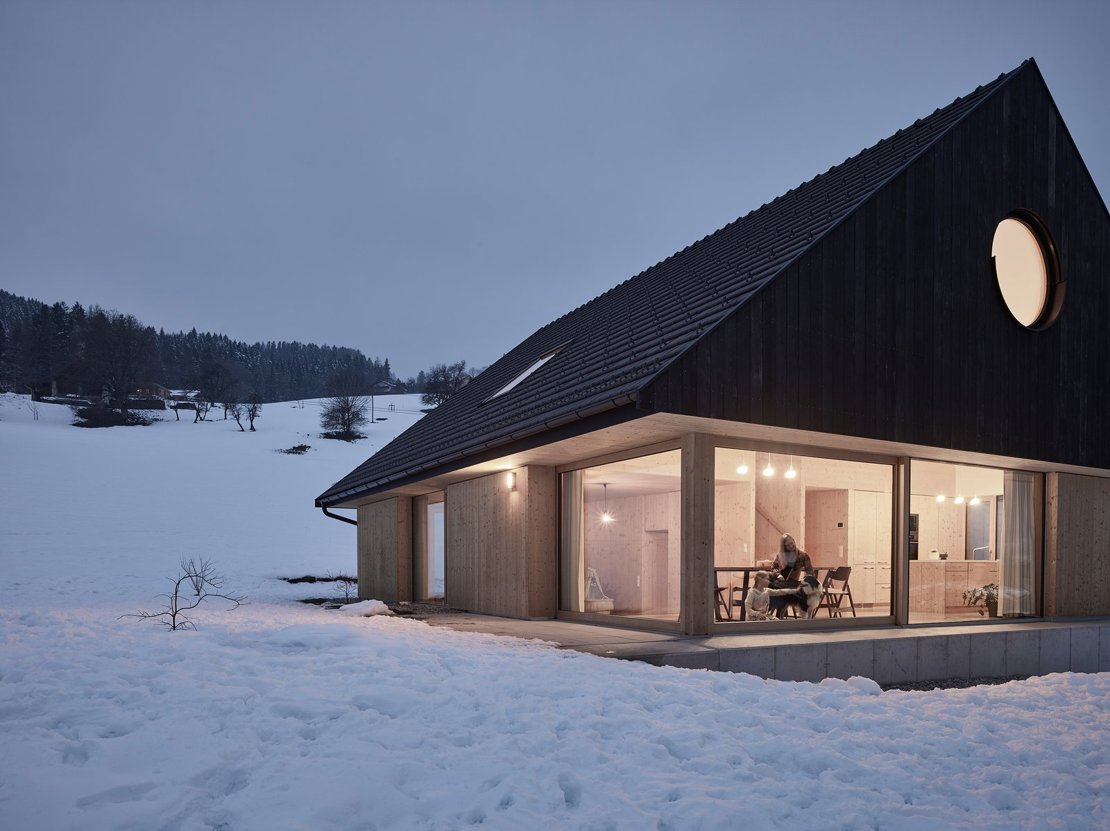Exterior, House Building Type, Wood Siding Material, Gable RoofLine, Cabin Building Type, Shingles Roof Material, and Metal Roof Material In summer, the living area is surrounded by grass that covers the terrain. Yet, once winter comes, this same area appears to be nestled within a blanket of snow.    Best Photos from This Sleek Austrian Home Turns Into a Cozy Light Box at Night