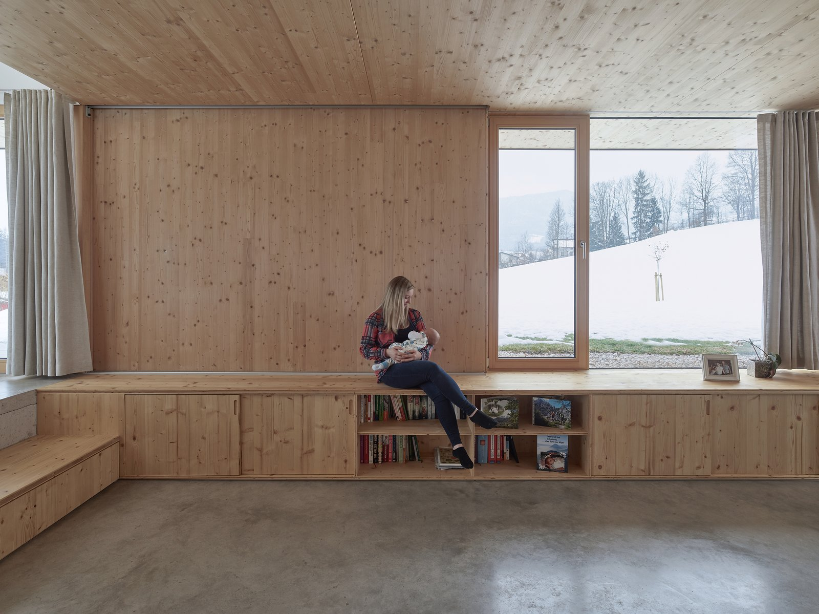 Living Room, Shelves, Bench, and Concrete Floor The massive windows that frame tranquil alpine views have been made from dual-lacquered laminated glass.     Best Photos from This Sleek Austrian Home Turns Into a Cozy Light Box at Night