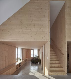 The lower floor is built at a high section of the slope—about 1.65 feet below the ground—to create a living area that's embedded within the terrain.