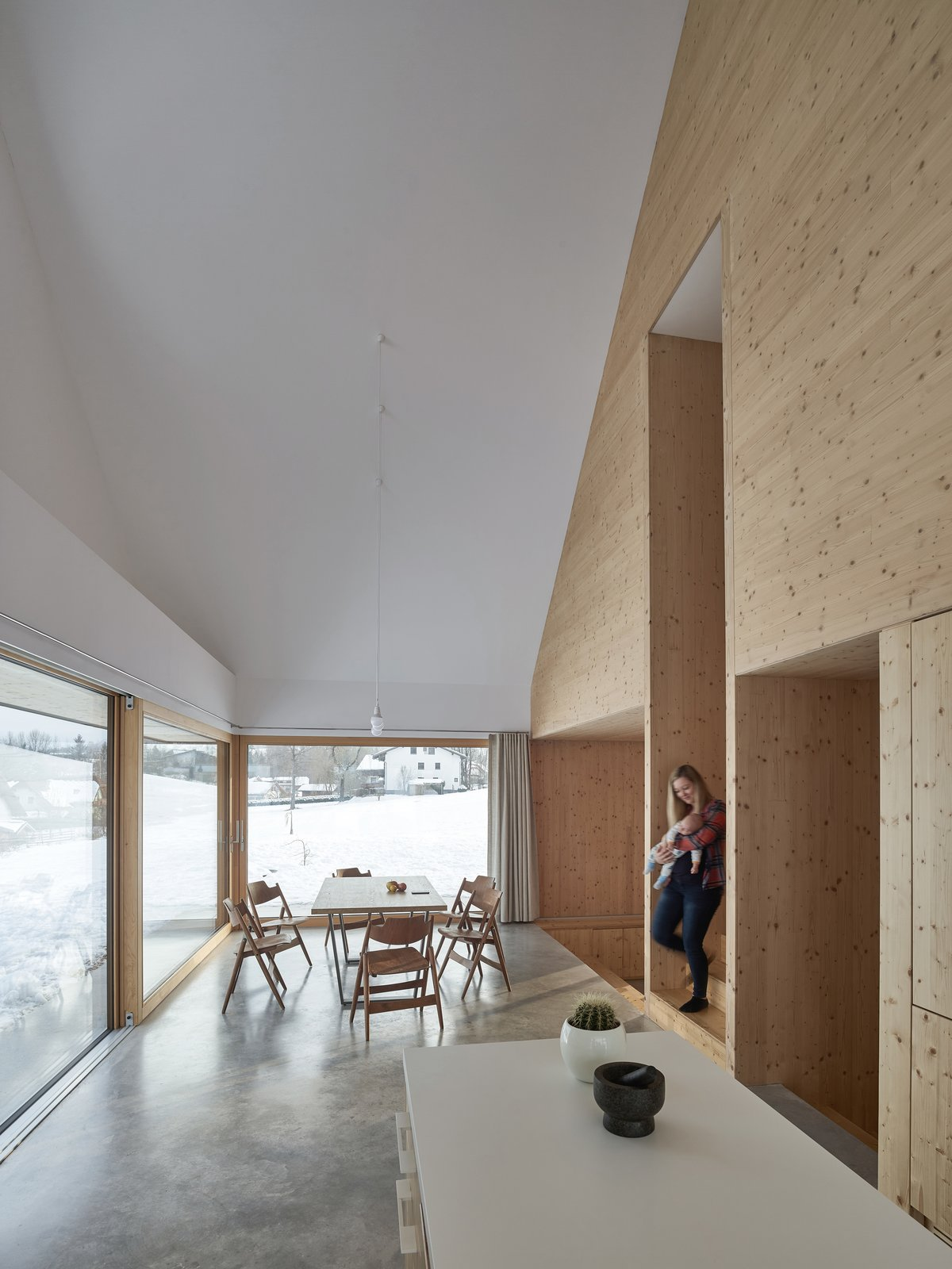 Dining Room, Chair, Table, Pendant Lighting, and Concrete Floor A staircase connects the dining area and kitchen on the ground floor to the bedroom on the upper level.    Best Photos from This Sleek Austrian Home Turns Into a Cozy Light Box at Night