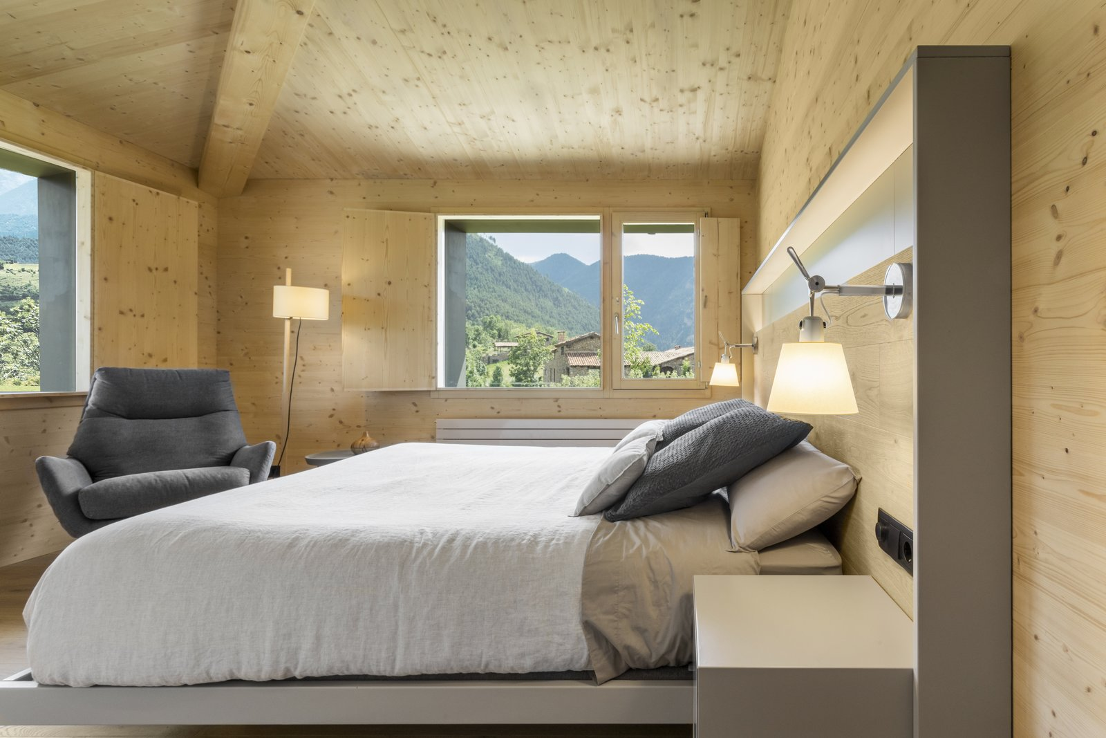 Bedroom, Floor, Chair, Bed, Light Hardwood, Night Stands, Wall, Lamps, and Accent The house has three bedrooms with ensuite bathrooms.  Best Bedroom Floor Table Photos from A Winning Residence in the Spanish Pyrenees Mixes Modern and Rustic
