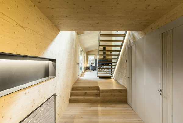 A hallway leads up to the open-plan living, dining, and kitchen areas.