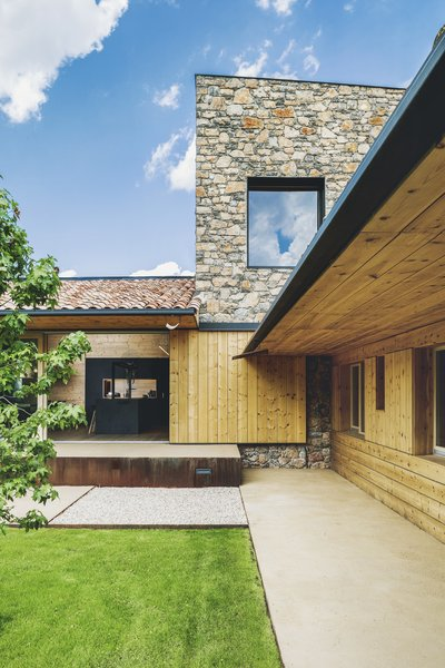 """The stone wall slightly protrudes above the roofs and highlights the simple forms guided by the plot's shape,"" says Elorduy. ""The wall draws a series of slopes and counter slopes providing the house with a singular geometry."""