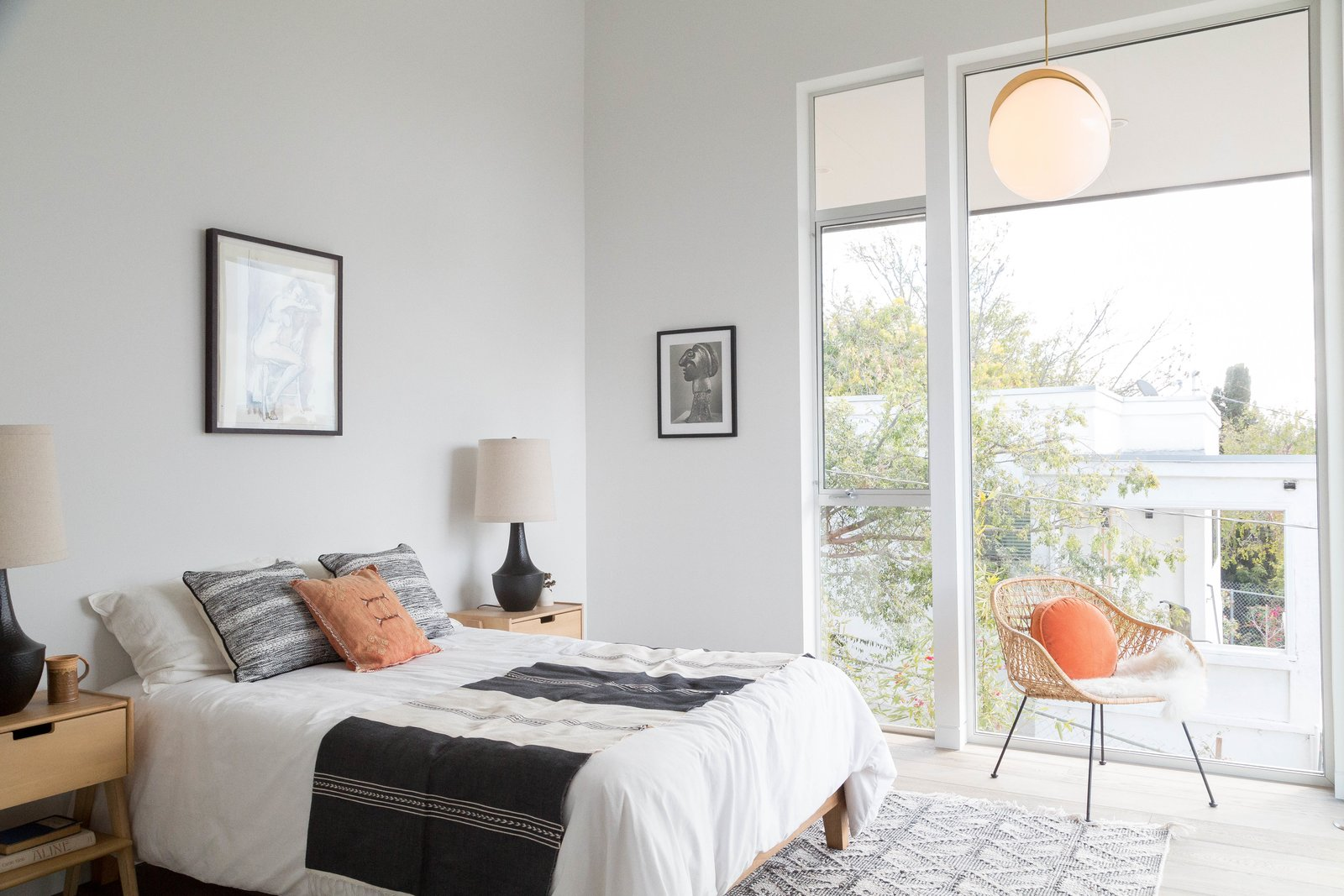 Bedroom, Rug, Chair, Bed, Pendant, Light Hardwood, Night Stands, Table, and Lamps The third level houses three bedrooms with ensuite baths.  Best Bedroom Light Hardwood Lamps Table Photos from A Tiered Home in Los Angeles Hugs a Steep Slope