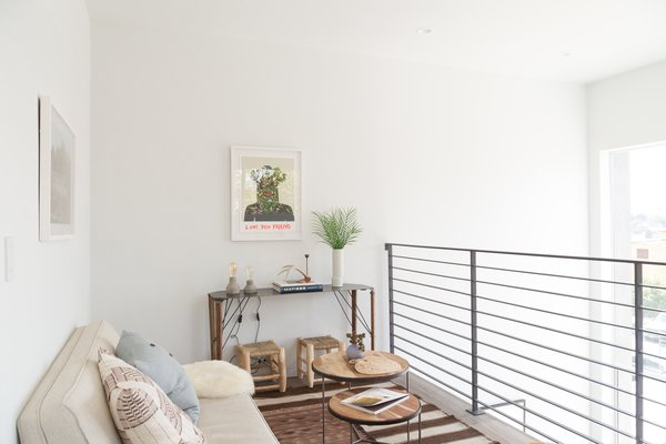 """The generous, double-height entrance lounge is equipped with washer/dryer utilities tucked under the stair with a cantilevered mezzanine """"book nook"""" right above it."""