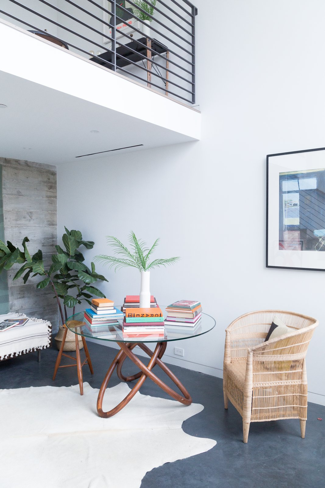 Living, Concrete, Chair, Recessed, Rug, Table, Stools, and Ottomans An entrance lounge and concealed laundry are located on the entrance level, where there is also a small lounge area with books.  Best Living Table Ottomans Photos from A Tiered Home in Los Angeles Hugs a Steep Slope