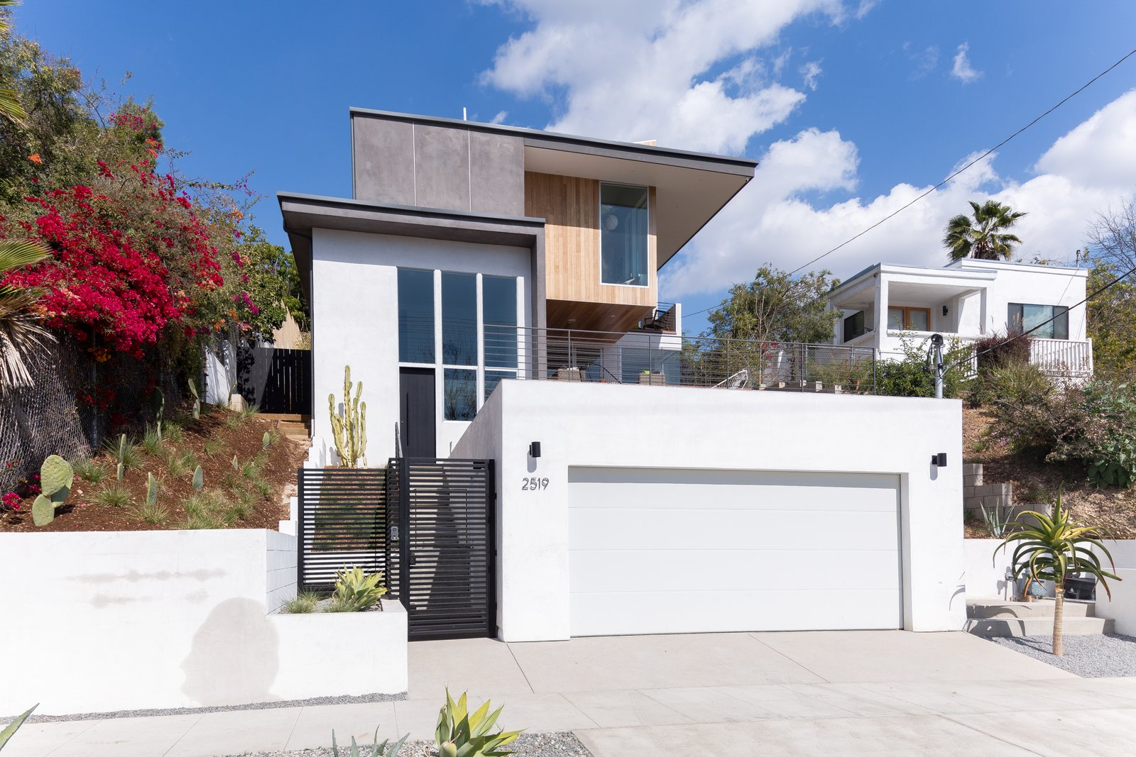 Exterior, House Building Type, Flat RoofLine, Wood Siding Material, Stone Siding Material, Metal Roof Material, and Stucco Siding Material Reinforced concrete was used for the retaining walls and slabs along all grades, while wood framing with steel framing beams were used at cantilevered areas.    Photo 2 of 17 in A Tiered Home in Los Angeles Hugs a Steep Slope