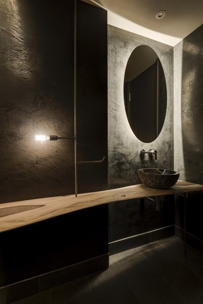 The guest bathroom features an organically shaped wooden table, which is suspended on copper and rests against the textured stucco wall.