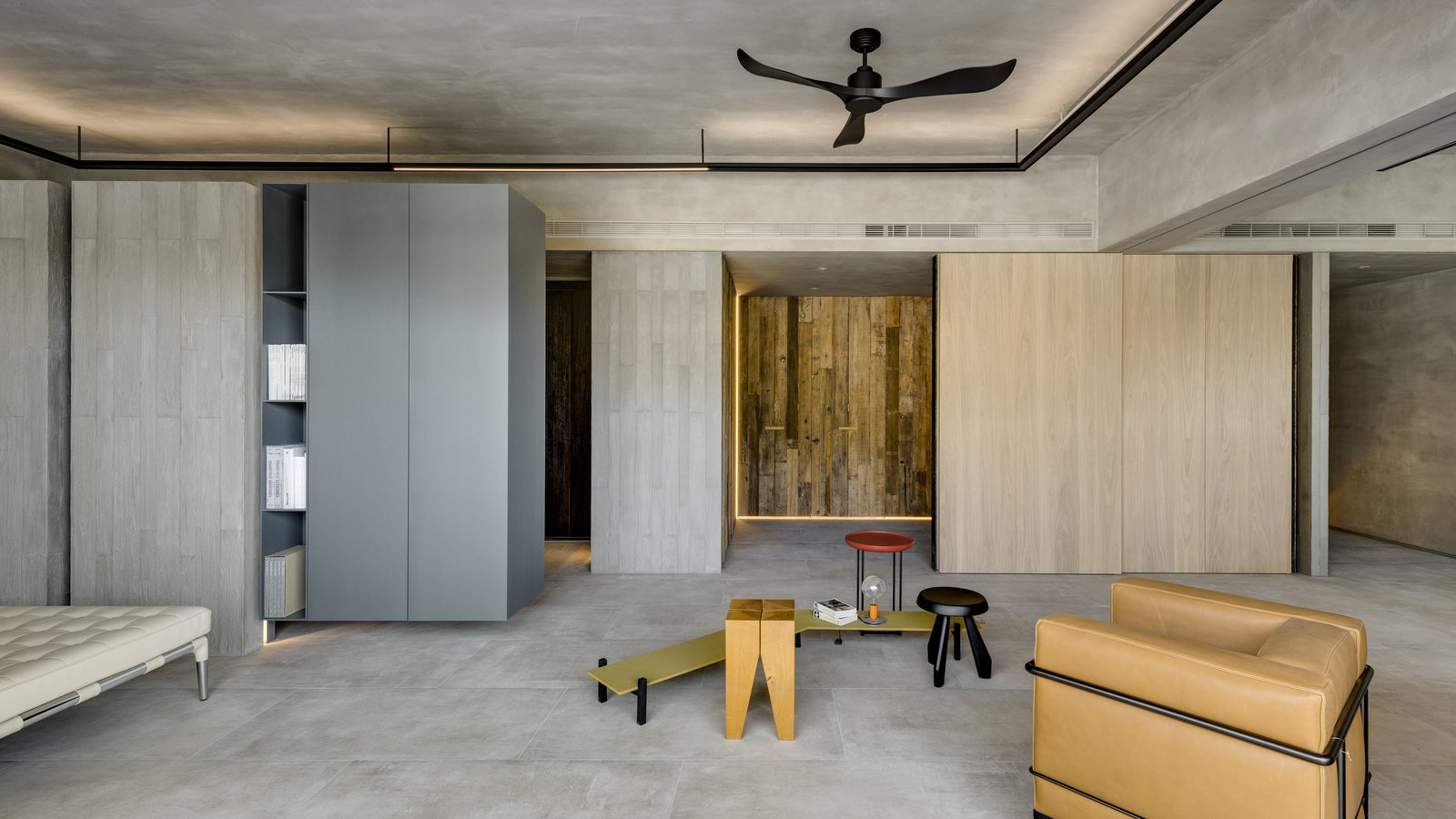 Living Room, Concrete Floor, Stools, and Chair Across from the curved structure is a wall clad in Taiwanese cypress panels.    Photo 5 of 16 in A Couple Embrace Wabi-Sabi Design to Travel Back to the Past