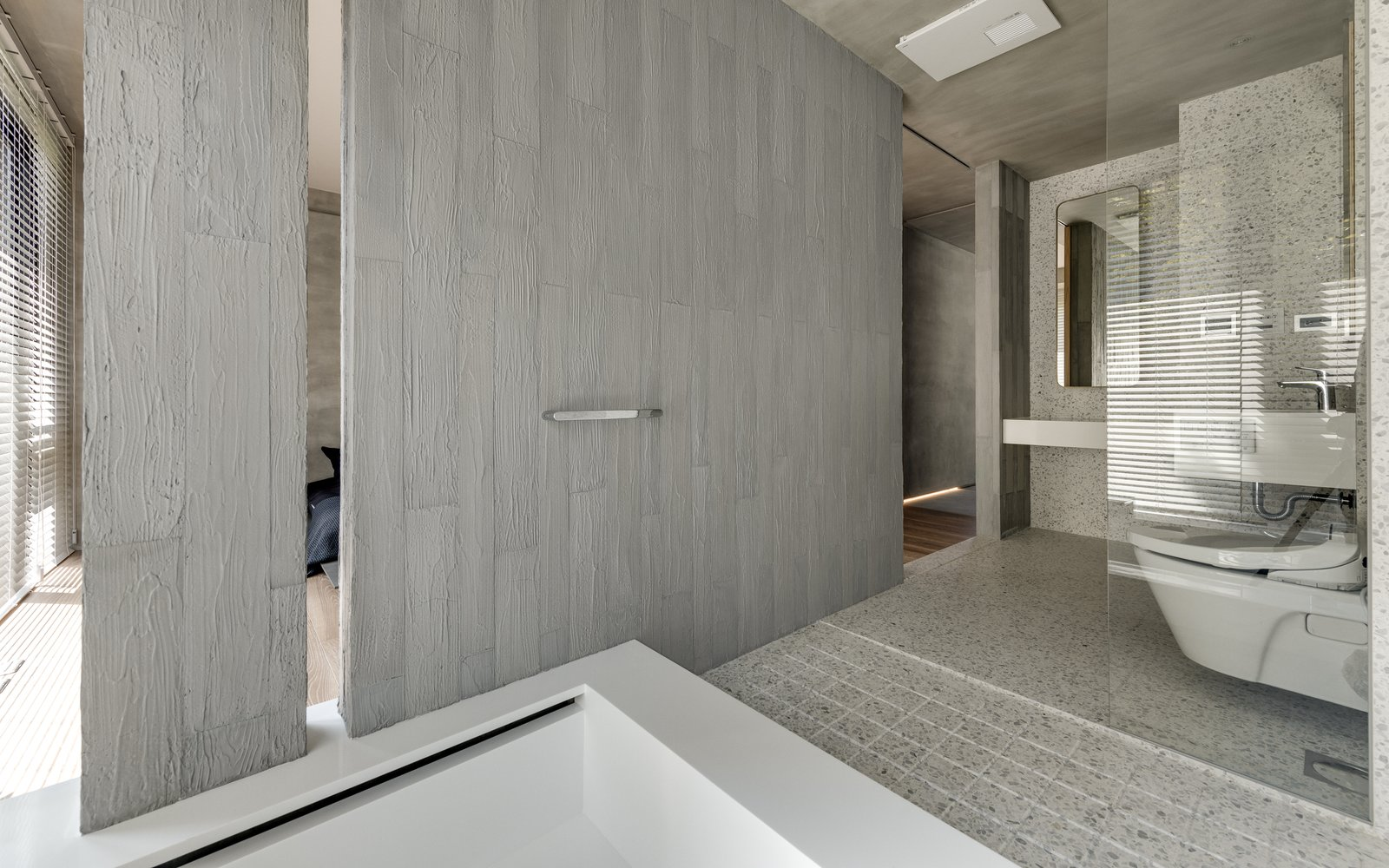 Bath Room, One Piece Toilet, and Terrazzo Floor A partition wall separates the master bathroom from the bedroom.    Photo 14 of 16 in A Couple Embrace Wabi-Sabi Design to Travel Back to the Past