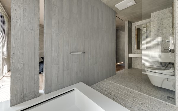 A partition wall separates the master bathroom from the bedroom.