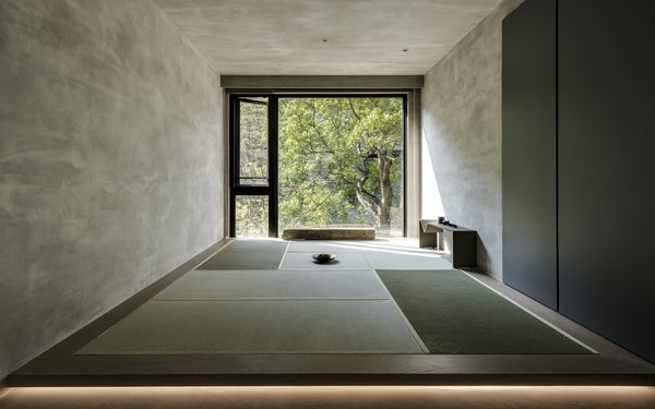 """A """"watshitsu"""" room, which is used for meditation and tea drinking, has a fully glazed wall that looks out to the verdant trees beyond the apartment."""
