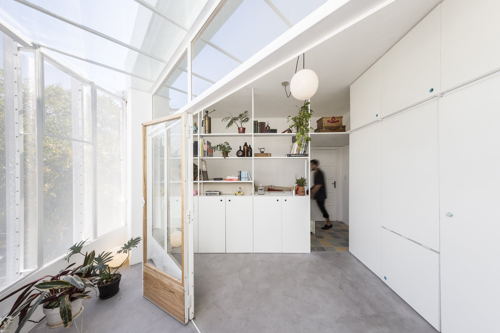 Living, Bookcase, Pendant, Concrete, Shelves, and Storage The space between the sleeping nook and balcony functions as a flexible living area.  Living Storage Pendant Concrete Photos from A Perforated Balcony Brings Ample Light Into a Tiny Abode