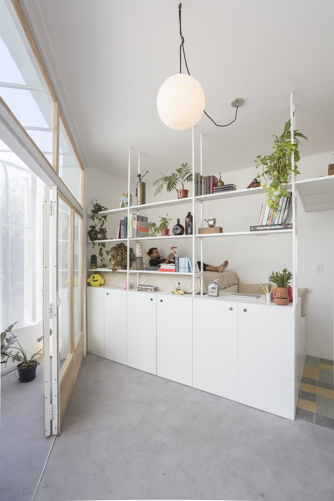 Bedroom, Pendant, Concrete, Bed, Storage, Shelves, and Ceramic Tile For the interiors, the architects have utilized every nook and cranny of the home to come up with smart storage solutions to maximize floor space.    Best Bedroom Shelves Pendant Photos from A Perforated Balcony Brings Ample Light Into a Tiny Abode