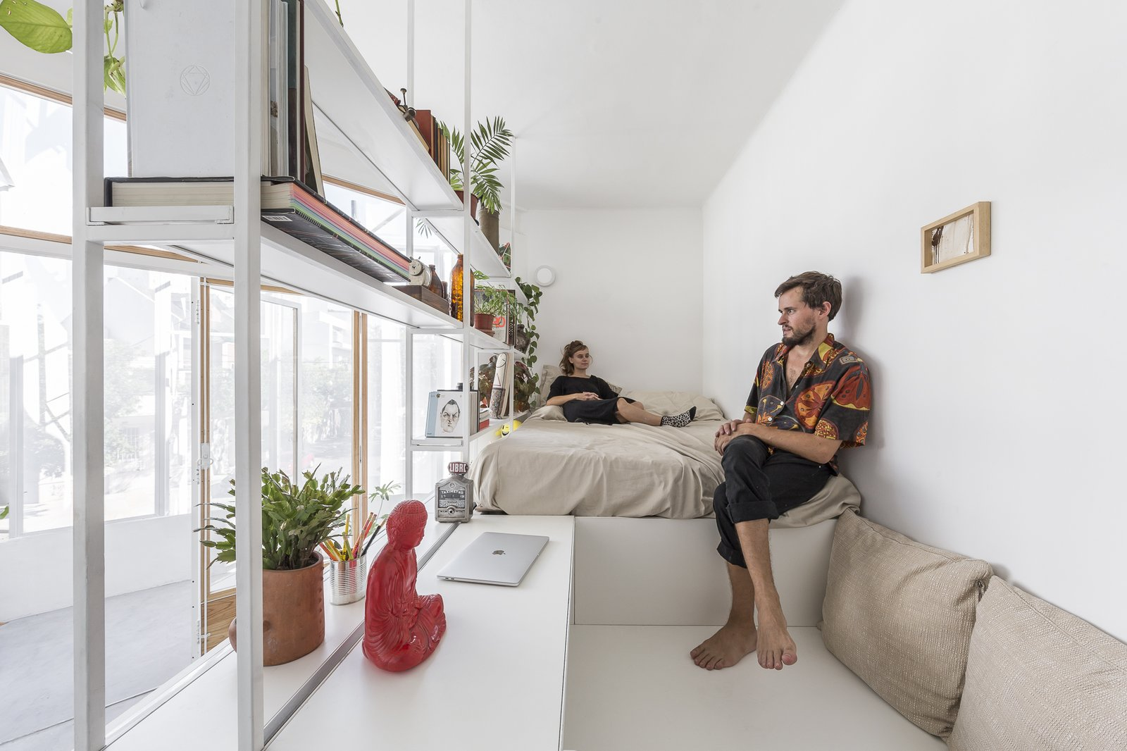 Bedroom, Bookcase, Storage, Shelves, Bed, Concrete Floor, and Wall Lighting The sleeping and study nook sit on a raised platform, and are surrounded by open shelving filled with books and plants.     Best Photos from A Perforated Balcony Brings Ample Light Into a Tiny Abode