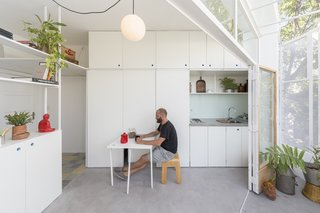 A pullout dining table is concealed within one of the white kitchen panels.