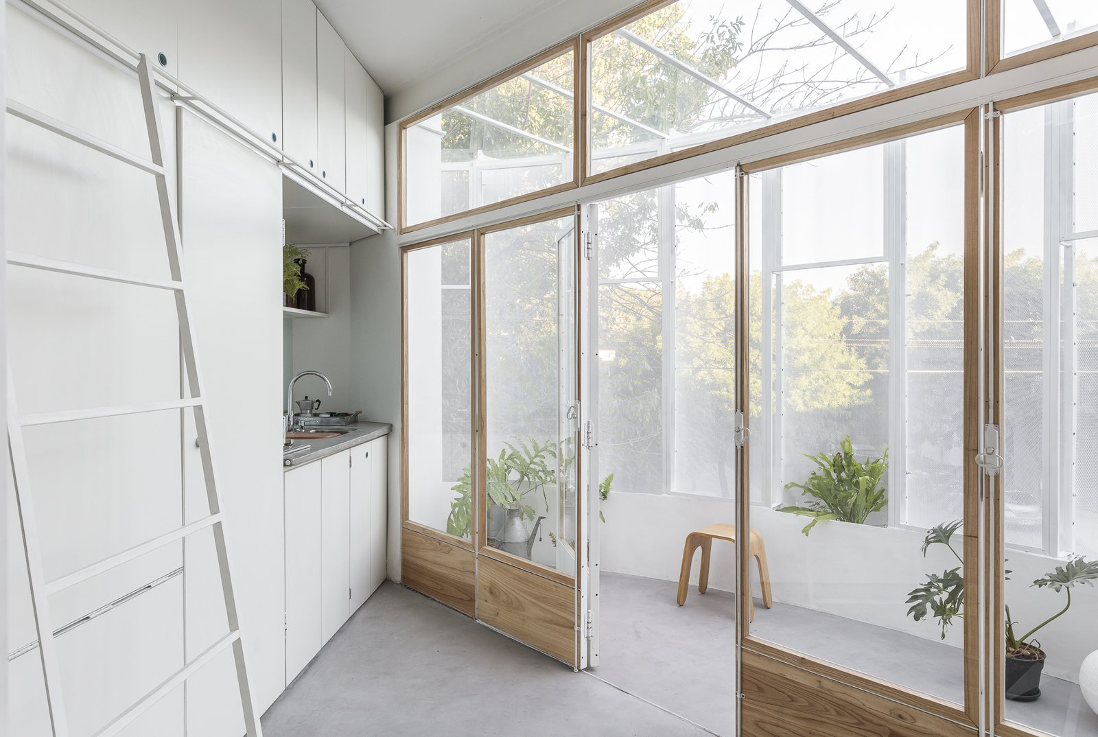 Kitchen, White, Concrete, Laminate, and Undermount Glazed, timber-framed folding doors separate the interior living area from the balcony.   Best Kitchen White Undermount Laminate Photos from A Perforated Balcony Brings Ample Light Into a Tiny Abode