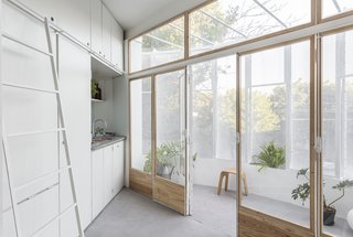 Glazed, timber-framed folding doors separate the interior living area from the balcony.