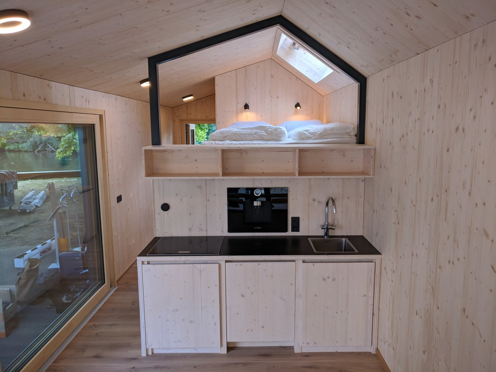 """Kitchen, Wood, Light Hardwood, Refrigerator, Drop In, Cooktops, and Wood The kitchenette includes a fridge, laundry machine, an integrated coffee machine, and a regular-size cooktop.  Best Kitchen Refrigerator Wood Drop In Photos from A Network of Prefab Tiny Homes Allows Users to """"Pay as You Live"""""""