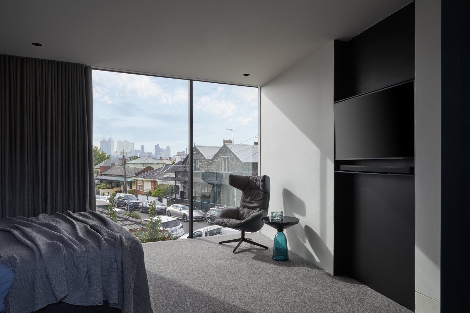 Bedroom, Recessed, Chair, Carpet, Ceiling, and Bed The extension's cantilevered upper level orientates the master bedroom toward the city skyline.   Bedroom Carpet Chair Ceiling Photos from An Old Kit Home Is Transformed Into a Multi-Generational Abode