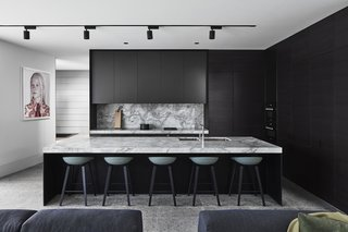B.E Architecture combines a revitalized kit home with a modern steel-and-glass extension to form a multi-generational Melbourne residence. In the kitchen, black cabinets meld seamlessly with dark countertops, furniture, and sleek track lighting.