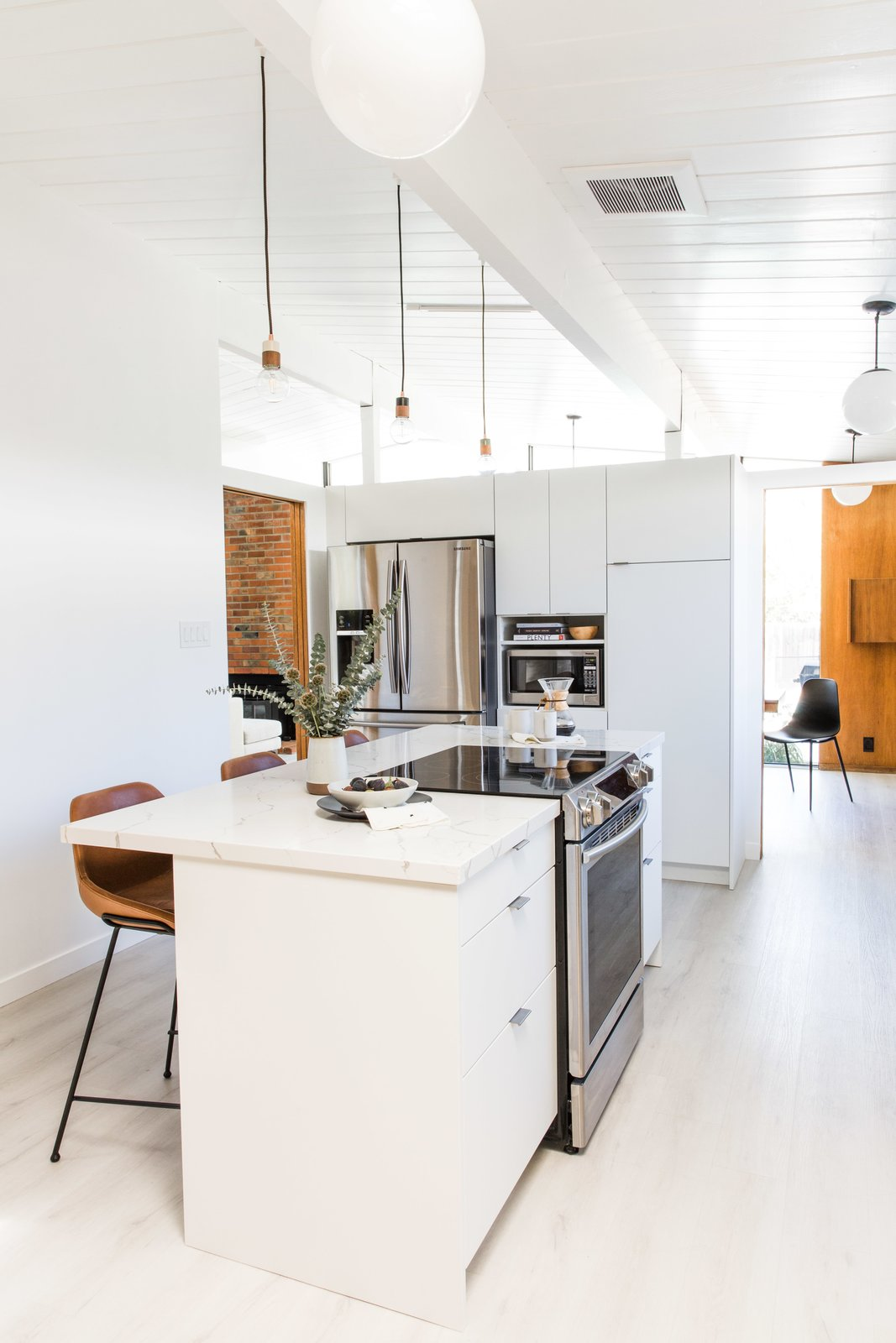 Kitchen, White Cabinet, Refrigerator, Cooktops, Range, Marble Counter, Pendant Lighting, Microwave, Undermount Sink, and Light Hardwood Floor Hong elevated the new IKEA kitchen with white slab fronts from Semihandmade.  Best Photos from Budget Breakdown: A Cramped Eichler Kitchen Gets a $49K Refresh