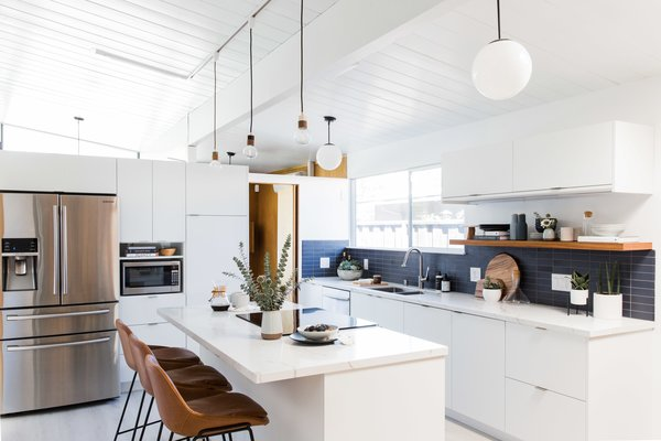 The once dim, cramped kitchen in this 1963 Eichler now features luxe vinyl tiling, white slab fronts from Semihandmade, and a dual-pane window, courtesy of Cathie Hong Interiors.
