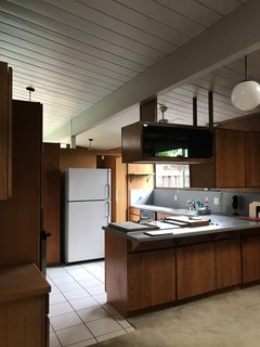 Before: Though floor-to-ceiling windows drew light into the home, the kitchen felt dark due to the mahogany wood panels.