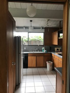 """Before: """"We debated whether or not to keep the wood paneling along the main wall of the kitchen, but because of the way that the wood panel was 'chopped' with the white beam above the window, we decided to remove it all and drywall it to make it look lot more clean and streamlined,"""" says Hong."""