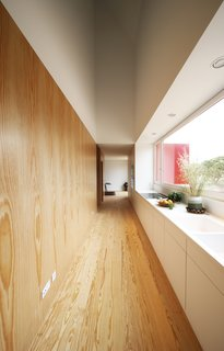 The elongated kitchen has a window that frames unobstructed views of the trees outside.