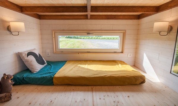 The simple, den-like sleeping nook can easily be converted into a storage space when needed.