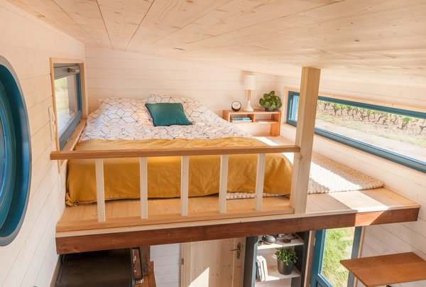 The lofted sleeping space features a double bed, a removable bedside table, and a balustrade which is attached to the floor as a safety precaution.
