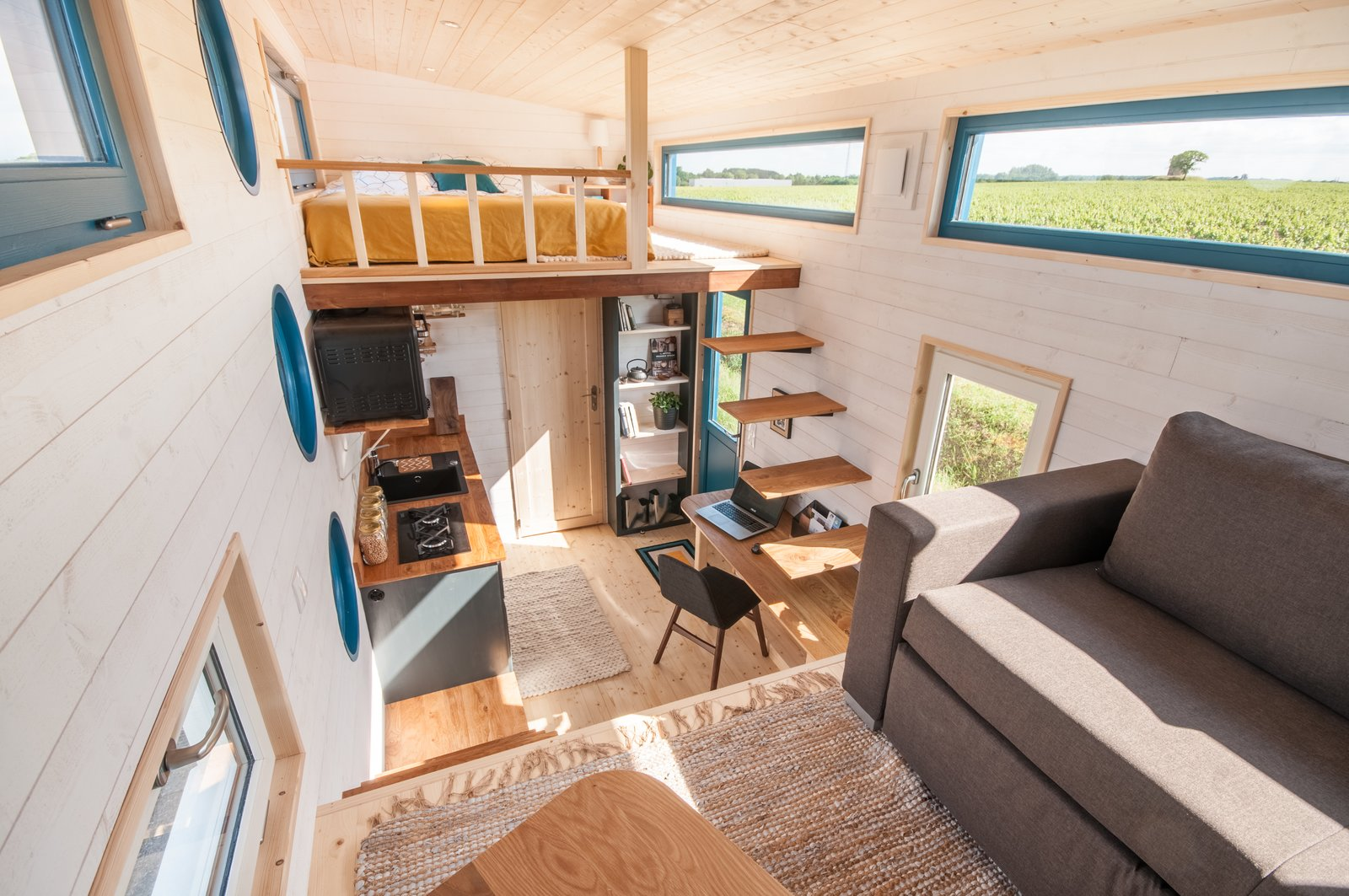 Living, Sofa, Shelves, Desk, Coffee Tables, Light Hardwood, Chair, and Recessed Across from the entrance door is the kitchen, which features a sink, small oven, hot water tank, fridge, and gas hobs.  Best Living Desk Chair Photos from This 140-Square-Foot Tiny House Is Packed With Surprises