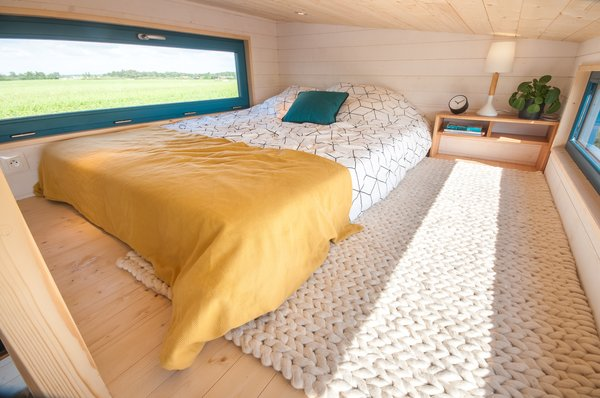 The bedroom enjoys views of the outdoors through windows on both sides.