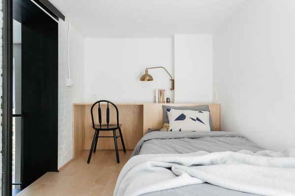 A work desk connects to the headboard.