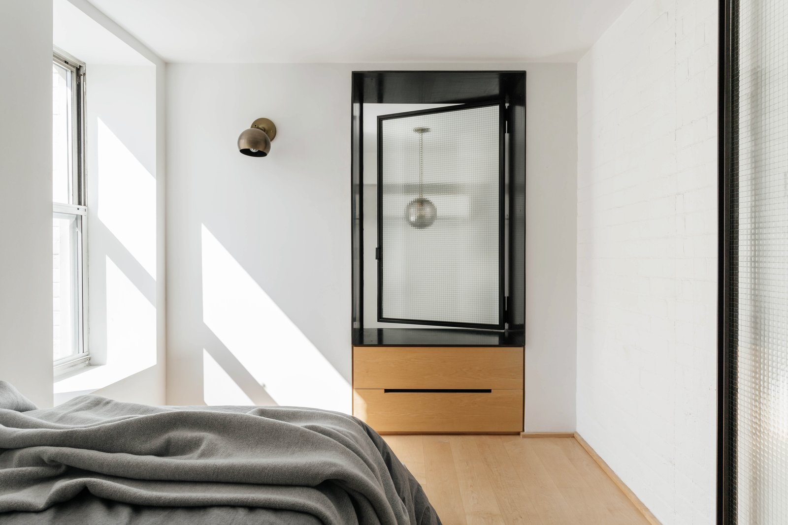 Bedroom, Light Hardwood Floor, Bed, Wall Lighting, and Pendant Lighting A wall sconce by Allied Maker.  My Photos from A Small Manhattan Home Gains  Space With Two Cozy Lofts
