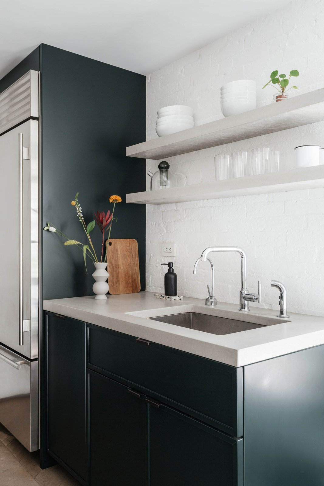 Kitchen, Refrigerator, Undermount Sink, Brick Backsplashe, and Colorful Cabinet A peek at the dark green, fuss-free kitchen.  Photo 9 of 14 in A Small Manhattan Home Gains  Space With Two Cozy Lofts