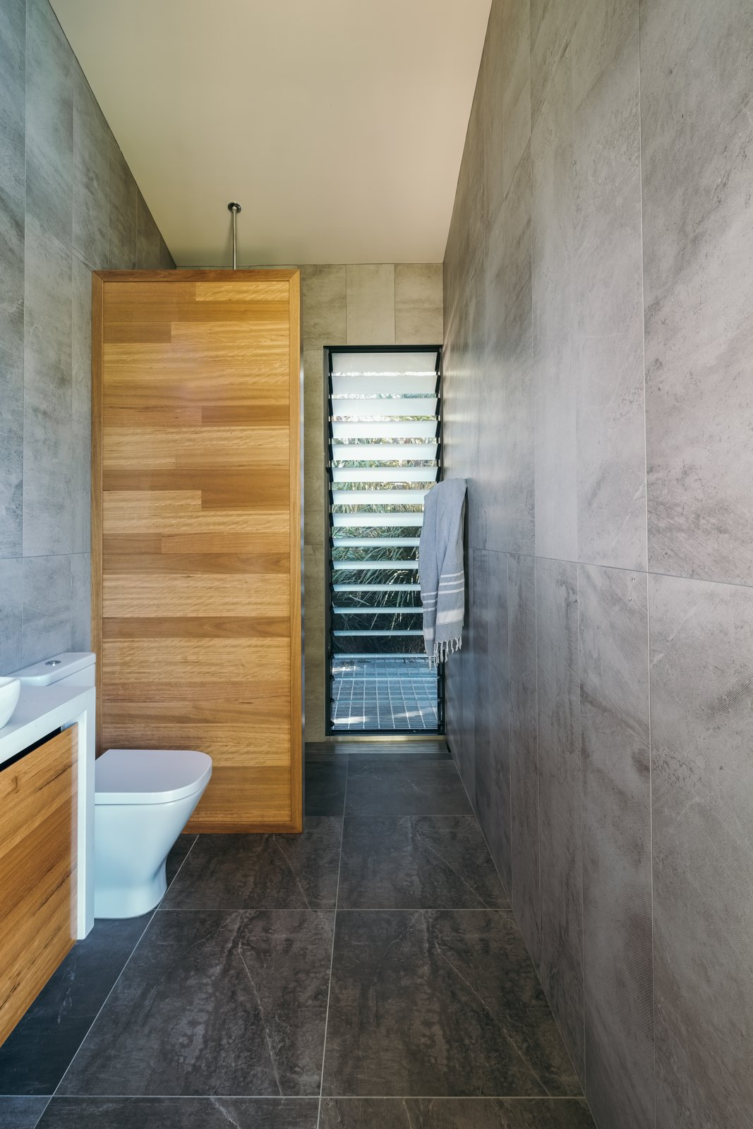 Bath, Stone Tile, Two Piece, Vessel, Engineered Quartz, and Slate The studio uses recycled water for all purposes.  Bath Stone Tile Two Piece Photos from A Tiny Guesthouse Hides in a Lush Australian Rainforest