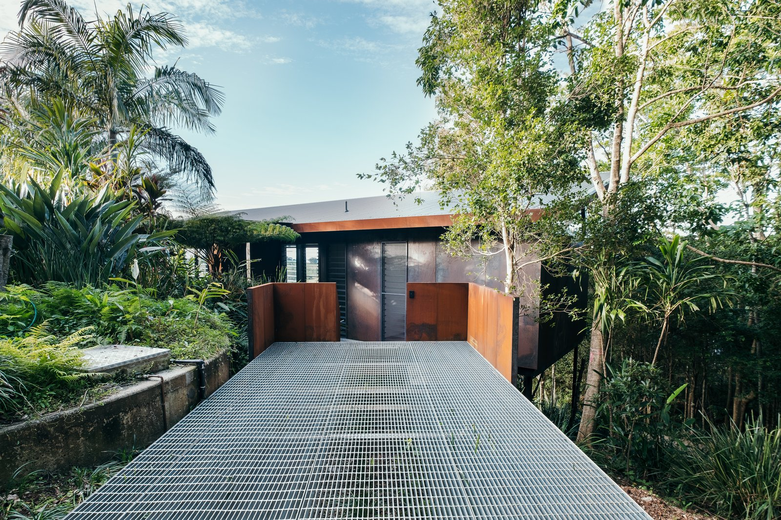 Outdoor, Retaining, Side Yard, Metal, Slope, Small, Stone, Wood, and Trees A ramp leads to the entrance door.  Outdoor Side Yard Slope Photos from A Tiny Guesthouse Hides in a Lush Australian Rainforest