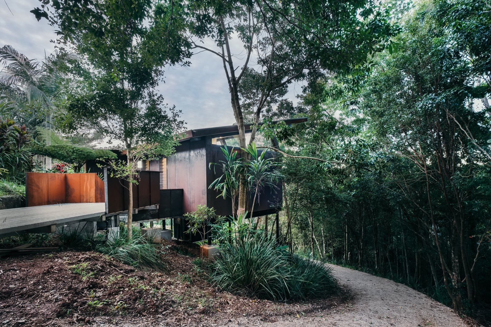 Outdoor, Small, Woodland, Trees, Wood, Vertical, Walkways, Wood, Shrubs, Side Yard, and Slope The home's low-maintenance Cor-Ten steel exterior can be easily washed down when needed.  Outdoor Side Yard Slope Photos from A Tiny Guesthouse Hides in a Lush Australian Rainforest